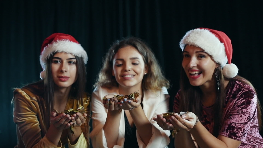 Three attractive women blowing golden colored confetti from hands wearing new year hats. | Shutterstock HD Video #1038788276