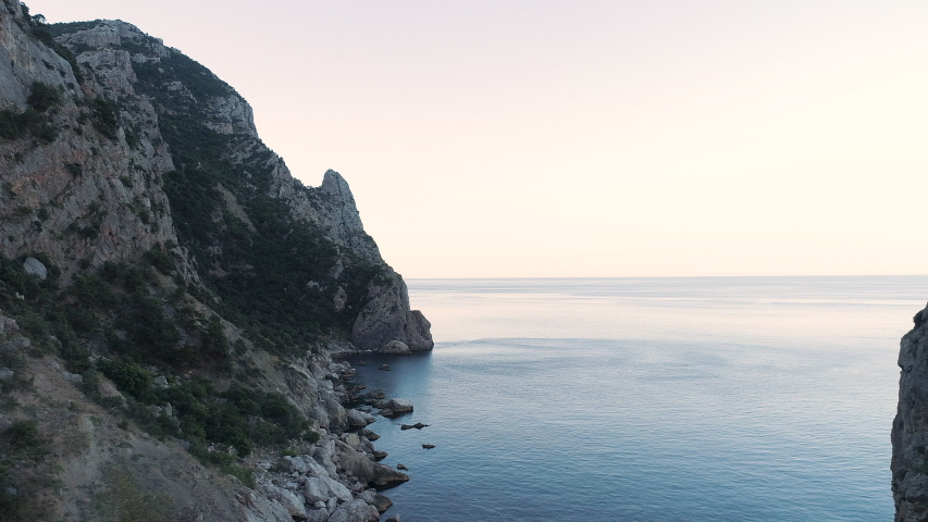 Aerial view of fantastic big rocks and calm ocean ripples at sundown time. Shot. Beauttiful natural landscape of the blue ocean water near huge steep cliffs. | Shutterstock HD Video #1038812486