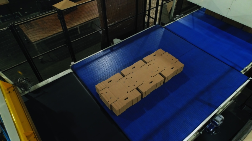 Pile of unfolded cardboard boxes transported by automatic production line conveyor in spacious workshop upper view | Shutterstock HD Video #1038922076