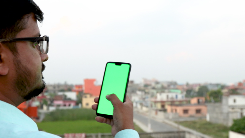 Man holding and using a smartphone with green screen | Shutterstock HD Video #1039008386