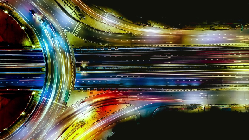 Aerial view of traffic time lapse on intersection circle. Busy traffic at night. Aerial view of road interchange or highway intersection with busy urban traffic speeding on the road at night. Thailand #1039034666