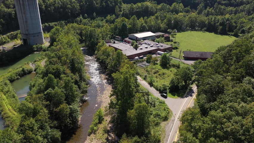 Aerial push in showing the Marsh Fork Elementary School next to a river with Montcoal mining operation with coal slurry pipelines in mountains of West Virginia.