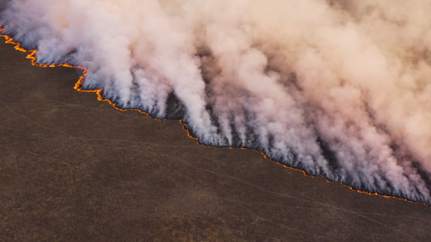 Climate emergency.High aerial fly over view of a grass fire in the Okavango Delta, caused by drought and climate change, Botswana | Shutterstock HD Video #1039131386
