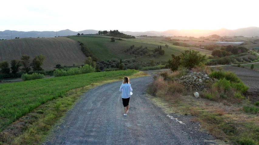 Beautiful young woman walking on a country road   Shutterstock HD Video #1039187876