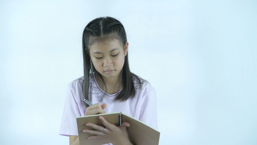 Educational concepts. The girl is taking notes in her notebook on a white background. 4k Resolution.   Shutterstock HD Video #1039197956