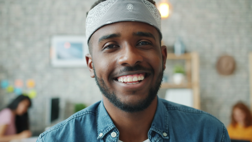 Close-up portrait of cheerful African American guy smiling indoors in office looking at camera wearing casual clothing and accessories. Youth and job concept. | Shutterstock HD Video #1039280576