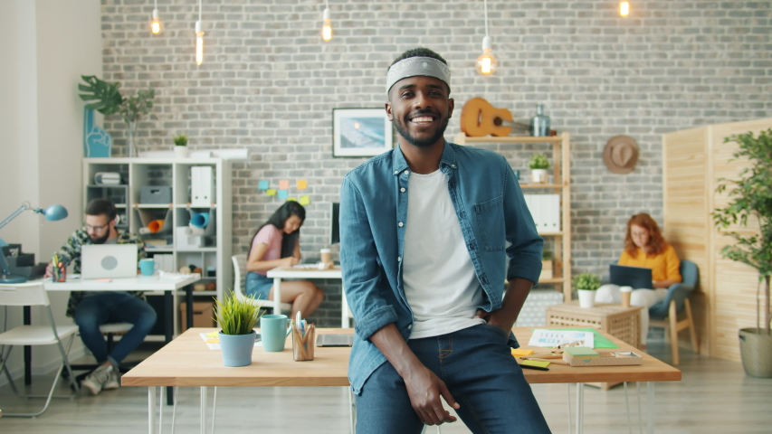 Slow motion portrait of joyful African American businessman smiling in office standing alone indoors while people working in background. Youth and business concept. | Shutterstock HD Video #1039280606