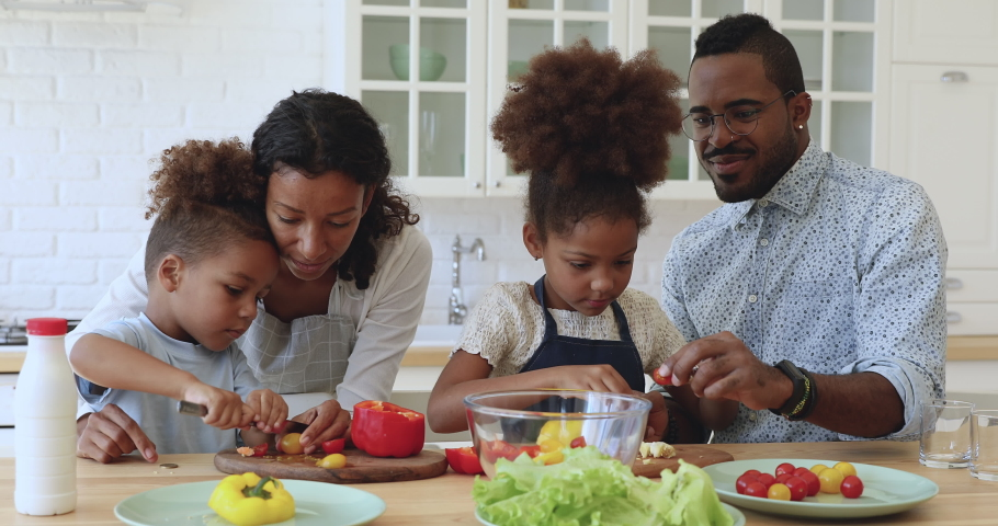 Cute little african american boy and girl help parents cutting fresh vegetables tomatoes pepper for healthy salad, happy mixed race family mom dad and kids girls cooking together in modern kitchen | Shutterstock HD Video #1039317596