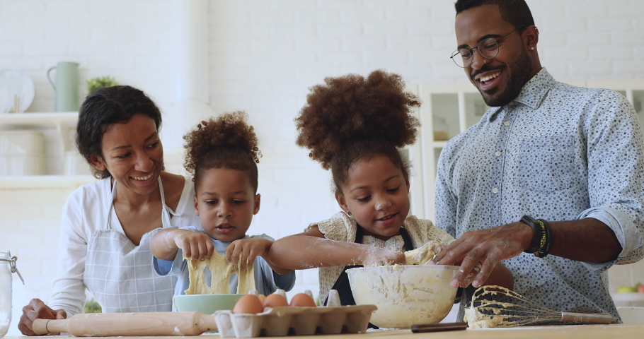 Cute funny small mixed race children son and daughter learn kneading dough with hands having fun help happy parents in kitchen, african family with little kids prepare cake cooking together at home | Shutterstock HD Video #1039317626