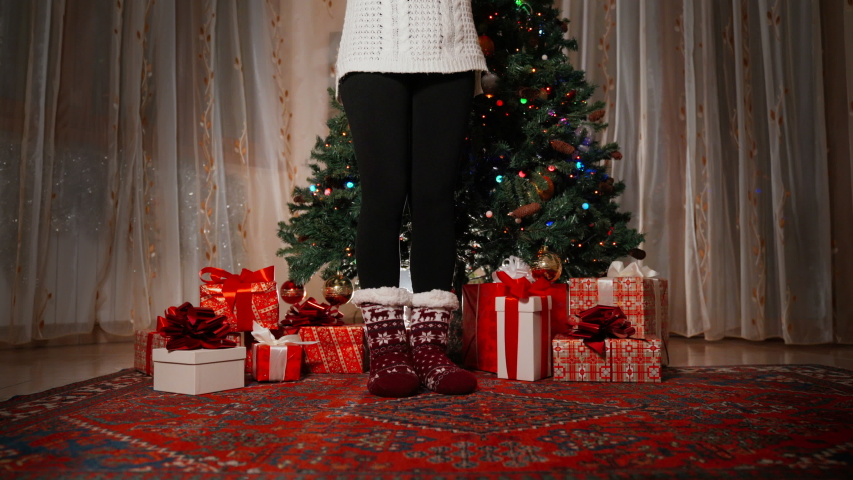 Close-up of slim woman's legs in knitted warm winter socks staying next to christmas tree decorations. Girl's legs and red christmas gift boxes under the tree. Flashing garland on the tree | Shutterstock HD Video #1039336226