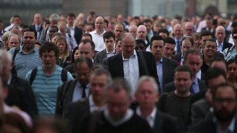 London - Circa 2014: A huge crowd of commuters make their way down the street on their way to work in the City of London.
