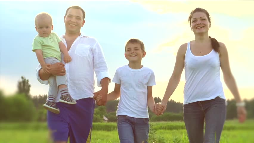 b65c953524e Happy Young Family with two children walking on summer field. Healthy  mother