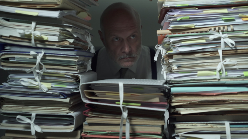Office clerk working behind a wall of paperwork: he is peeking from a hole and stamping a document, bureaucracy concept | Shutterstock HD Video #1039418756