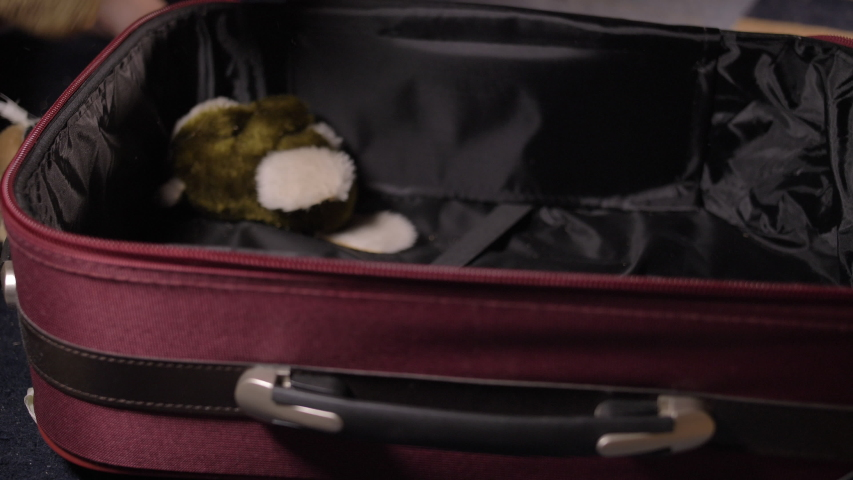 Boy puts toys in a suitcase, getting ready for the road, travel concept | Shutterstock HD Video #1039463096