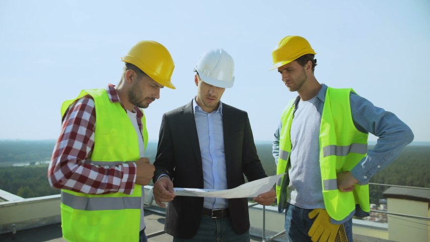 Young male boss in safety helmet discussing construction plan with workers #1039557596