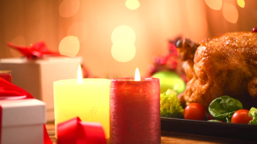 Christmas Roasted Chicken Dinner. Winter Holiday table served, decorated with candles. Delicious Steamed Roast chicken over wooden background with Christmas gifts, table setting. Dolly shot 4K UHD | Shutterstock HD Video #1039678286