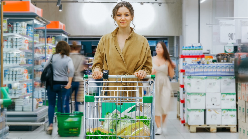 Young pretty smiling woman with full shopping cart stands in modern supermarket among buyers zoom out time lapse   Shutterstock HD Video #1039721966