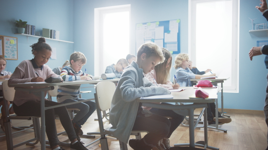 Row of Brilliant Young Kids in School Writing in Exercise Notebooks, Taking a Test. Elementary Classroom of Diverse Bright Children Writing in Notebooks. Arc Slow Moving Camera | Shutterstock HD Video #1039967006