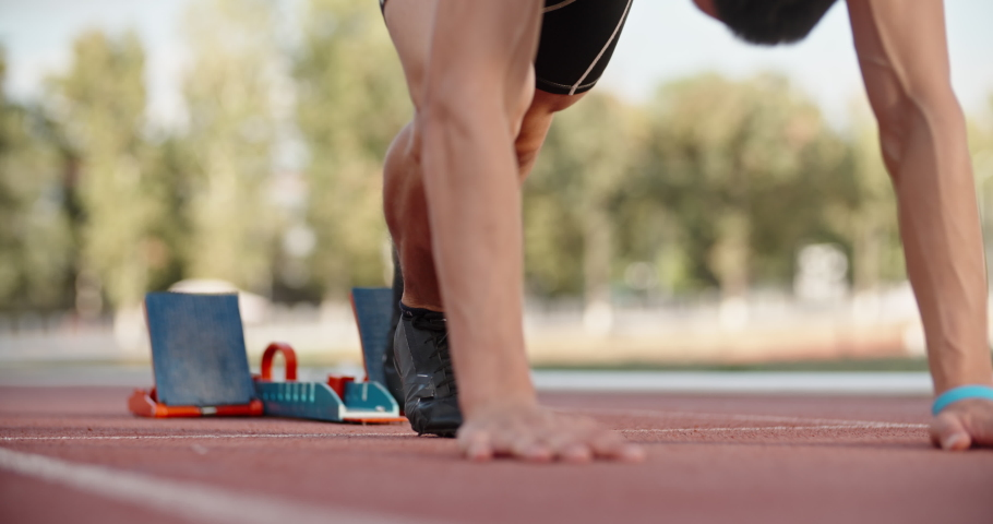 Low angle shot of an athlete putting feet on starting blocks on stadium track, blasting off and having a quick start - sports concept 4k footage #1040007566