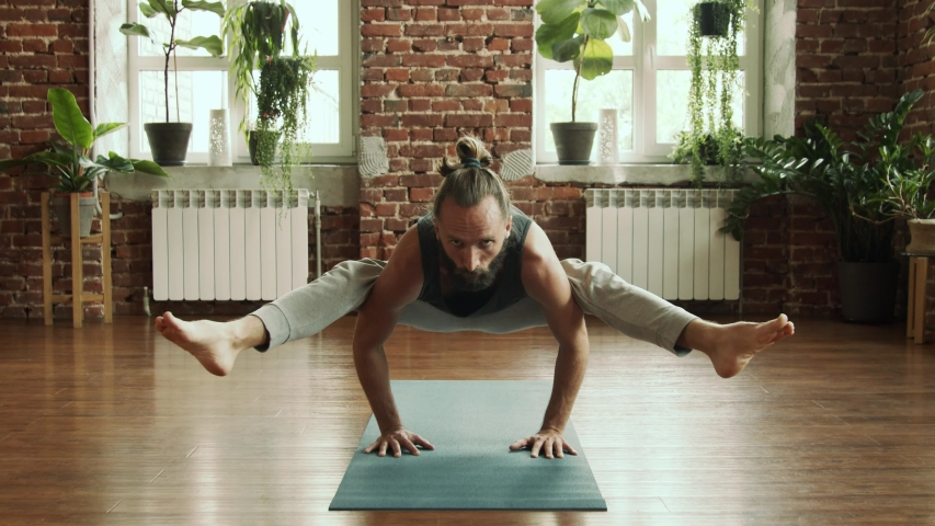 Man practice yoga pose in studio with brick wall and green plants. Fitness and healthy lifestyle concept. Bearded male making balance yoga pose in gym in slow motion. Find his harmony inside.  | Shutterstock HD Video #1040355896