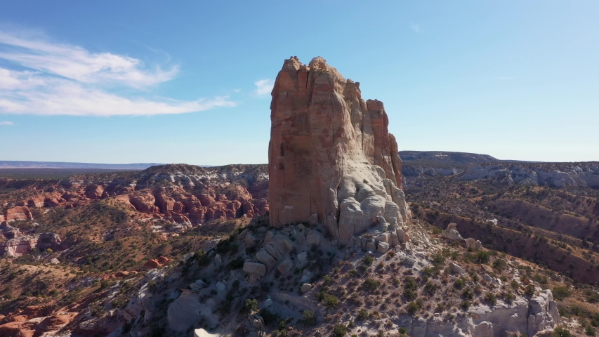 High remnant monument of red beige canyon rocks in the red sandstone desert of western United States. Picturesque beautiful landscape of desert nature and sandstone erosion. Aerial back from the cliff | Shutterstock HD Video #1040440286