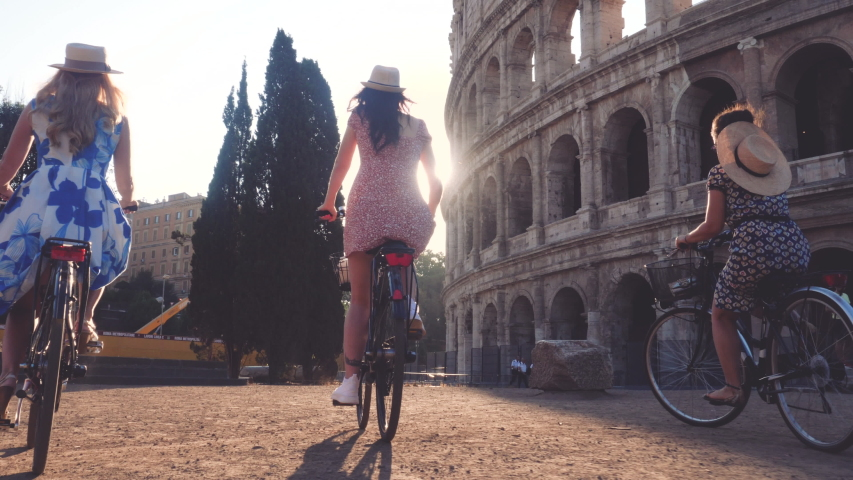 Three happy young women friends tourists riding bikes at Colosseum in Rome, Italy at sunrise. | Shutterstock HD Video #1040681756