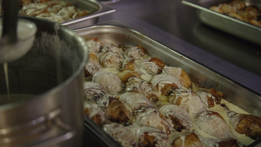 Closeup of chef hand pouring baked chicken with white sour cream sause in buffet cafeteria. cook, preparing, banquet, appetizing, meat, canteen catering business concept | Shutterstock HD Video #1040698826