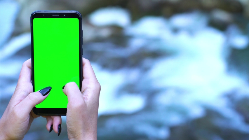 Technology in nature concept: smartphone with green screen waterfall cascade background chromakey tracking matte vfx ready shot natural organic sport challenge abstract 4k | Shutterstock HD Video #1040706536