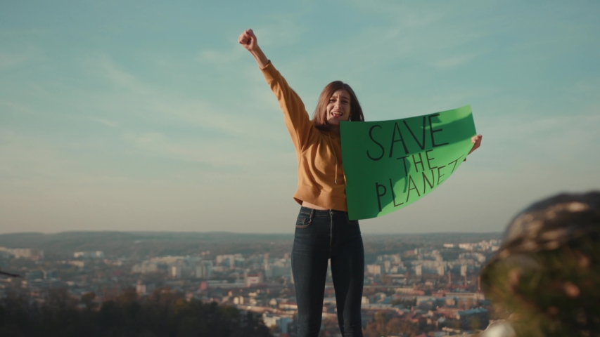 Activist woman holding encouraging green poster Save the Planet standing calls out slogans around plastic bag background beautiful view nature community earth eco outdoor recycle trash waste | Shutterstock HD Video #1040738186