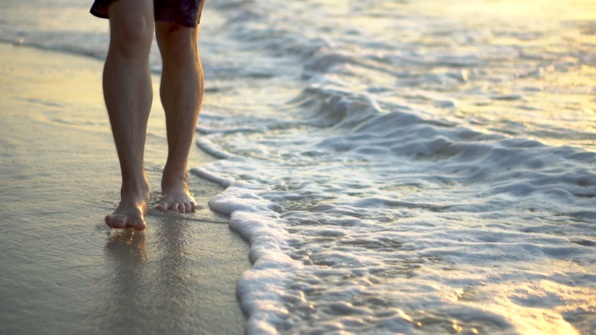 Male Feet Walking Through Waves Crashing at Beach With Colorful Sunset Colors Reflecting | Shutterstock HD Video #1040818466