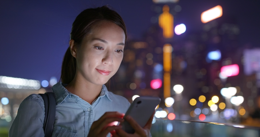 Woman use of mobile phone at night in city   Shutterstock HD Video #1040822426