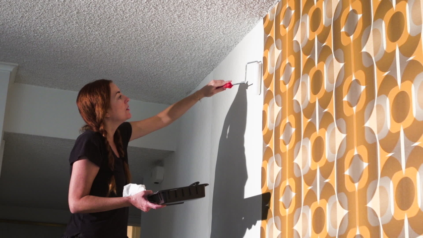 Real woman improving, renovating and decorating her home by hanging 1970's retro wallpaper | Shutterstock HD Video #1040883176