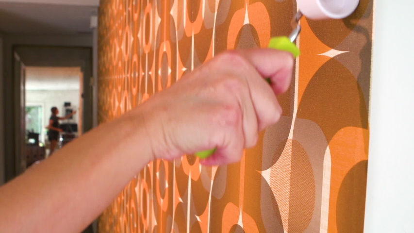 Real woman improving, renovating and decorating her home by hanging 1970's retro wallpaper | Shutterstock HD Video #1040883206