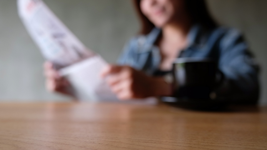 Blurred of a woman reading newspaper while drinking coffee in the morning | Shutterstock HD Video #1040895146