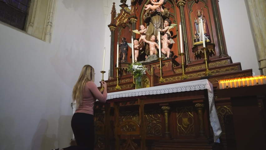 This video shows a young caucasian woman kneeling at catholic alter and praying.