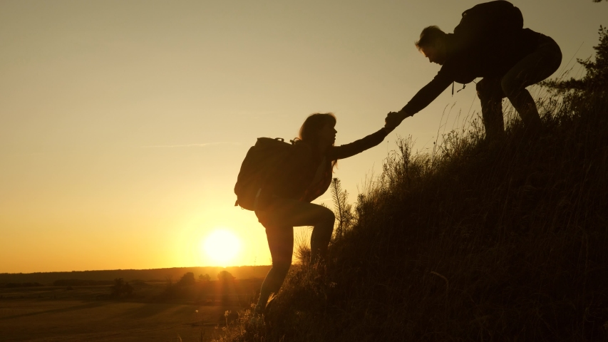 Tourists climb the mountain at sunset, holding hands. teamwork of business people. Traveler man holds out woman's hand to a traveler climbing to the top of the hill. Happy family on vacation. #1040943776