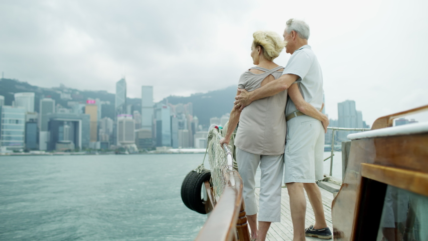 Happy Caucasian senior couple on a luxury anniversary world tour vacation trip enjoying the city skyline of Victoria harbor Hong Kong Asia RED MONSTRO | Shutterstock HD Video #1040996786