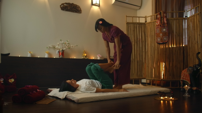 Asian Woman performs Traditional Thai Massage to beautiful European Woman. Rehabilitation and Treatment after Injuries with the help of Massage. Relax and Rest from massage of Legs, Arms and Back. | Shutterstock HD Video #1041046556