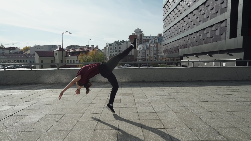 Young female gymnast runs in the city and doing a series of flips on training area near modern buildings. | Shutterstock HD Video #1041083776