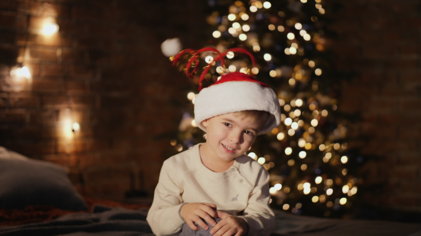Funny little boy of 4 years old in Santa's hat with spring playfully shakes his head looking at the camera while sitting on the bed in the bedroom with a decorated Christmas tree with garlands. | Shutterstock HD Video #1041142666
