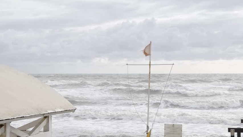 Flag waving in the stormy wind on the sea of ​​Ostia in Rome | Shutterstock HD Video #1041148486