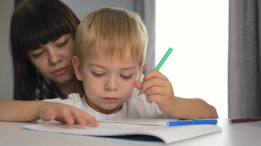 Happy family. Mom and son paint a picture in the album. Home schooling. Doing homework. Teamwork | Shutterstock HD Video #1041222046