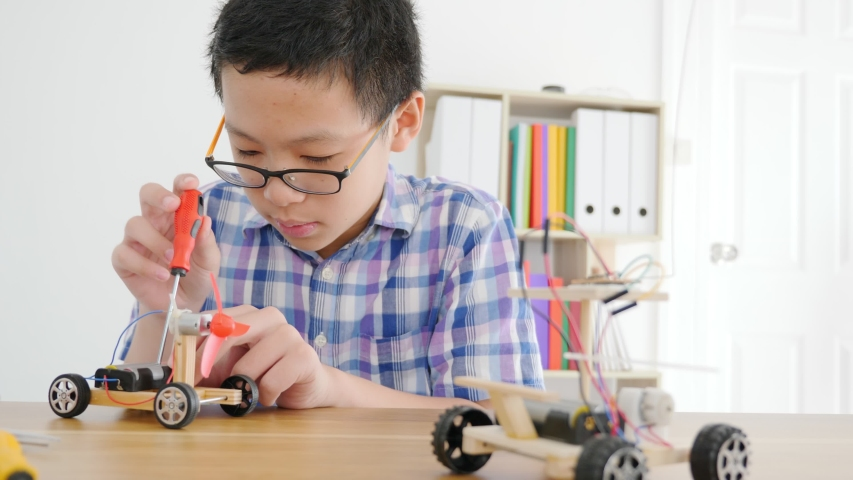 Young Asian boy creating a toy car that is powered by wind from propellers.   | Shutterstock HD Video #1041312136