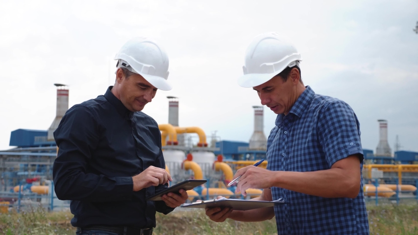 Teamwork. Two helmeted engineers are testing the operation of a gas processing plant. Teamwork Success and Victory Concept #1041324406