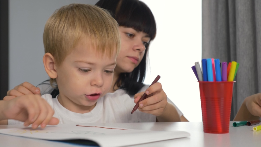 Happy family. Mom and son paint a picture in the album. Home schooling. Doing homework. Teamwork | Shutterstock HD Video #1041325186