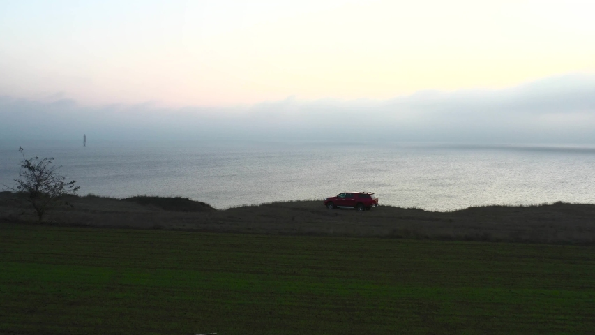 A large red pickup truck stands on a wild seashore with incredible views of the sea during sunset. The incredible beauty of nature. Ukraine. Lonely lighthouse at sea   Shutterstock HD Video #1041458806