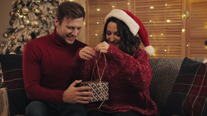 Lovely Young Couple Finalizing together Christmas Gift Bandaging Tape and Tied in a Bow Sitting on the Sofa near Christmas Tree at Home Background. Concept of Holidays and New Year | Shutterstock HD Video #1041460276