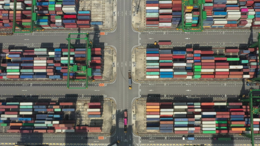 Aerial view of the port of Singapore with trucks and thousands of colored containers ready to be loading on the cargo ships. The Port of Singapore is the second biggest port in the world.   Shutterstock HD Video #1041512026