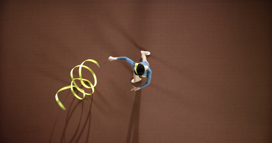 Girl gymnast performs exercises with a yellow ribbon. Top view. Slow mo, slo mo, slow motion, high speed camera | Shutterstock HD Video #1041554236