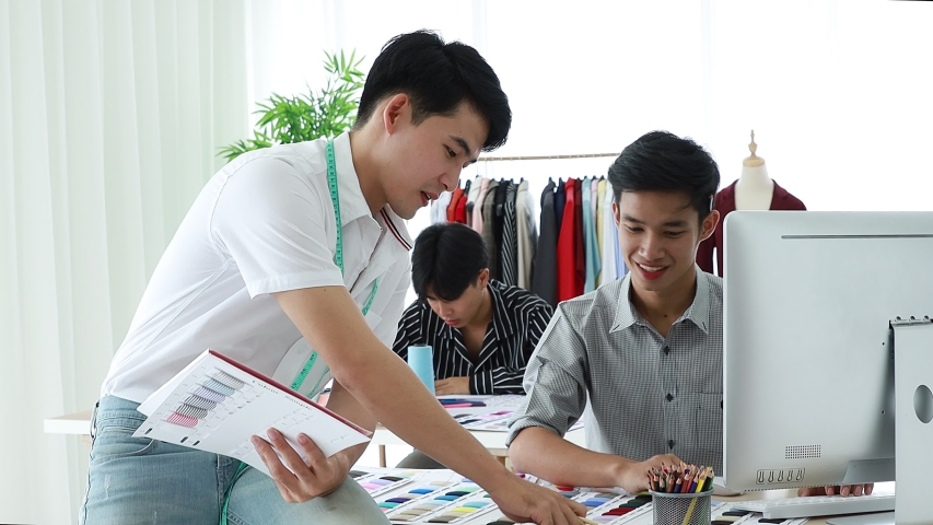 Asian handsome male fashion designer is selecting fabric from fabric sample catalogs and order subordinates to order the material for sewing as a dress for the fashion show of the new collection.  | Shutterstock HD Video #1041558376